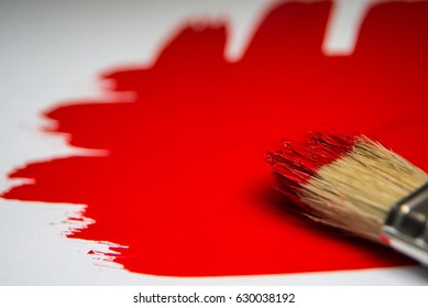 Red color and paintbrush on white background