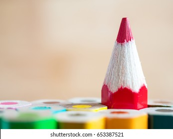 Red color pencil stand on various color pencil with wood blur background (Leadership concept)