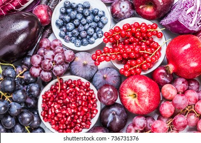 Red color and purple fruits and vegetables background top view.