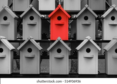 Red color wooden birdhouse stand out from the crowd. Metaphor to business concept. Stands out among the gray of similar objects. Notable among the competitors.
