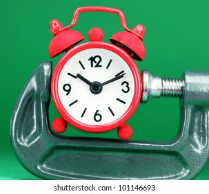 A red colored  alarm clock placed in a Grey clamp against a pastel green background, asking the question do you manage your time effectively.