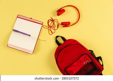 red colored earphone school bag and notebook on yellow background