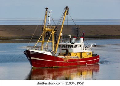Red colored fishing trawler in a sunny harbor in front of a breakwater and blue sea