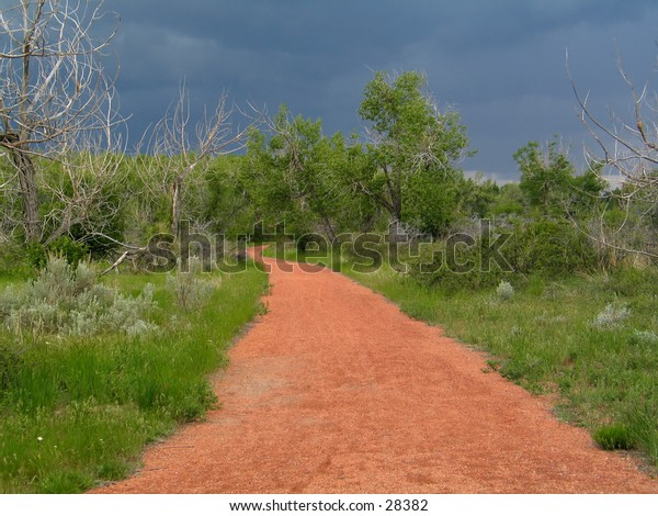 Red colored gravel path, surrounded by grass and trees, stormy skies in the background