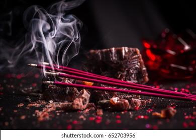 Red colored incense sticks burning against a dark background made up of natural black rock salt