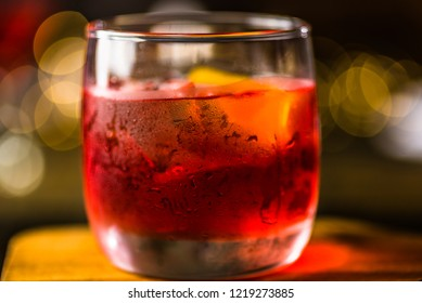 A red colored negroni cocktail made of one part gin, one part vermouth rosso, and one part Campari, shown in a shallow deopth of field.