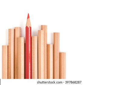 Red colored pencil stand out of other brown pencils - business concept of leader and success - isolated object on white background