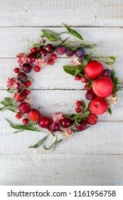 Red colored wreath made of autumn harvest goodies on a wooden background. Flat lay style, vertical view. You can write your text in the middle