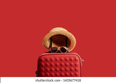 red colorful travel bag with straw hat and sunglasses isolated on red