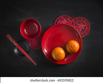 Red colour Chinese traditional style eating utensils and tangerine on moody black rustic table top. Flat lay image.