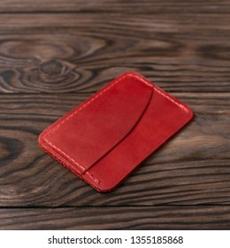 Red colour handmade leather one pocket cardholder on wooden background. Stock photo with soft blurred background.