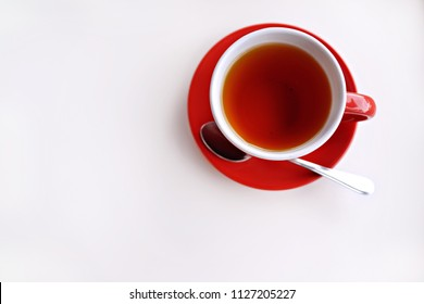 Red colour tea cup and saucer on white background, top view with copy space