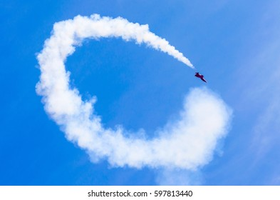 Red combat fighter with white circle smoke behind in the blue sky.
