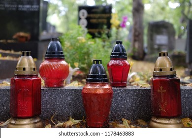 Red commemorative candles on a stone grave plate in the cemetery