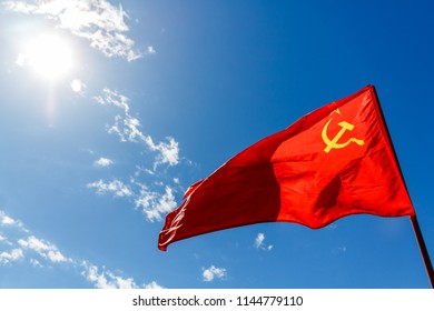 Red communist flag of the USSR against the blue sky with white clouds and sun.