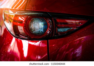 Red compact SUV car with sport and modern design are washing with water. Car care service business concept. Car covered with drops of water after cleaning with high pressure water spray. Luxury lamp.