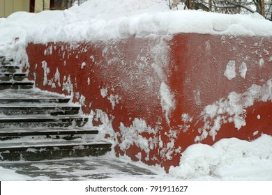 The red concrete wall is covered with white snow. Winter holiday background