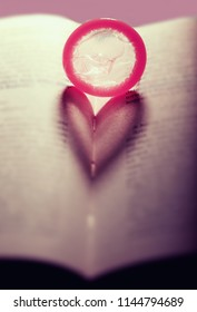 Red condom heart on the open book