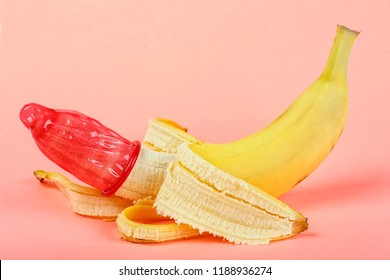 Red condom on yellow banana, pink background.