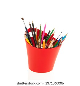 Red container full pencils and brushes isolated over white background
