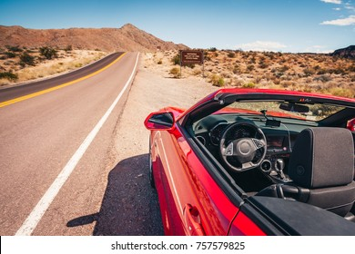 Red convertible with the top down stopped on a shoulder on a desert road
