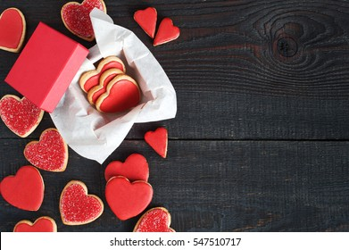 Red cookies with red icing and box on the old brown wooden table