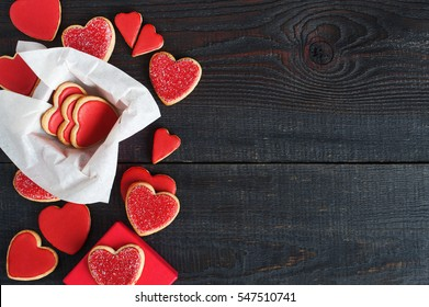 Red cookies with red icing and box on the old wooden table