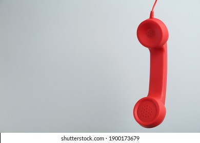 Red corded telephone handset hanging on light grey background, space for text. Hotline concept