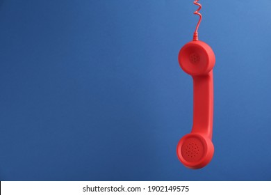 Red corded telephone handset hanging on blue background, space for text. Hotline concept