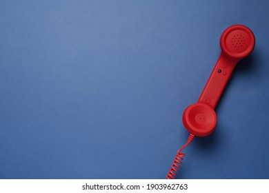 Red corded telephone handset on blue background, top view. Hotline concept