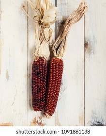 Red corn cobs on a wooden table