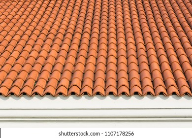 Red corrugated tile element of roof at house and white wall. Shingles roofing surface tiles overlay pattern and texture