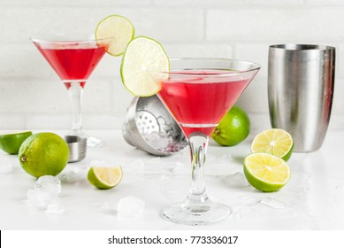 Red cosmopolitan cocktail with lime in martini glass, on white marble background copy space