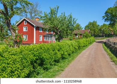 Red cottage by a gravel road in the Swedish countryside