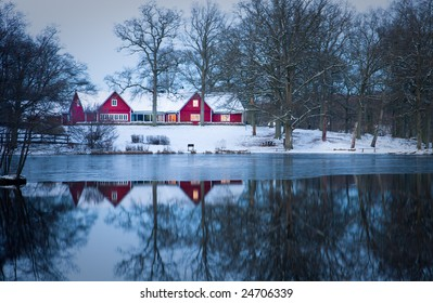 Red cottage in front a lake in winter (Sweden)