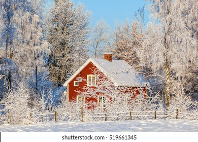 Red cottage in winter forest with frost and snow