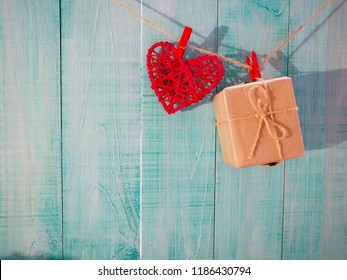 red country fabric hearts hanging on clothesline with rustic wood door; Valentines Day, Mothers Day, and love concept background with wooden copy space