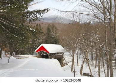 Red covered bridge in a snowy forest