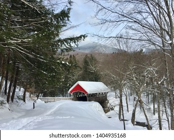 Red covered bridge in a snowy forest, The Flume Franconia Notch, White Mountain National Forest, New Hampshire