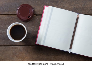 Red covered opened book blank page with pencil and black coffee in white plastic cup and brown cap on old wooden table