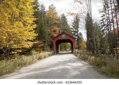 Red covered wooden bridge with an American flag in Vermont, countryside