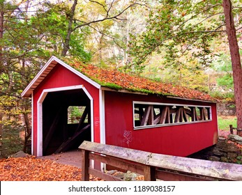 A red covered wooden bridge inside Southford Falls State Park in the fall in new england New Haven Connecticut United States.