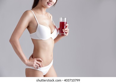 red cranberry for Health concept - Beautiful slim body of woman and orange juice isolated on gray background
