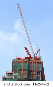 Red crane above building construction site against blue sky background