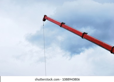 A red crane against cloudy sky