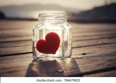Red crochet heart in glass bottle with sunlight and wooden background, Love concept, Valentine's Day, Vintage style