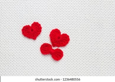 Red crochet wool heart and ribbon on white crochet background. The concept for 14 February, romantic Valentine day. Red heart made of wool yarn. Festive overhead photo with place for text, copyspace