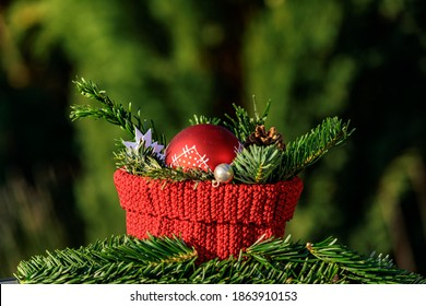 A red crocheted basket with fir branches and a red Christmas tree ball against a green background