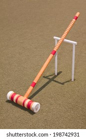 A red croquet mallet resting against a hoop