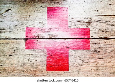 red cross on wooden background